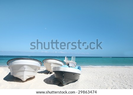 Boats on a tropical white sand beach with the view of a caribbean ocean
