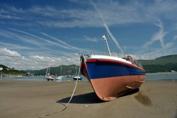 Boats on the beach at Barmouth town with the harbour and landmark railway bridge over the estuary of the river Mawddach and Cardigan Bay, the marina and quay in Gwynedd, North Wales, UK.