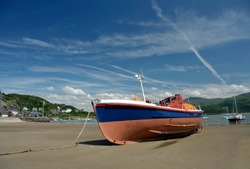 Boats on the beach at Barmouth with the harbour on the estuary of the river Mawddach and Cardigan Bay, the marina and quay in Gwynedd, North Wales, UK.