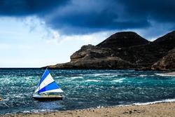 Boats on the beach under stormy sky in Cabo de Gata, Almeria, Spain.