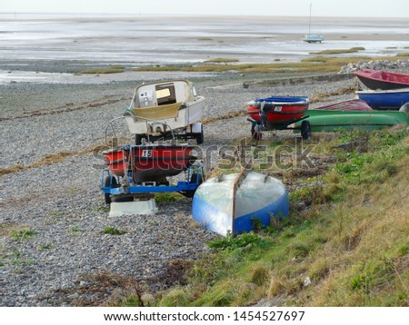 Boats on trailers and upturned on sea shore pebble beach