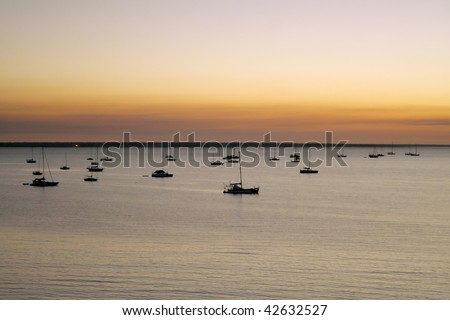 Boats resting at sunset over sea.