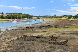Boats, sailing ships and wrecks at low tide in the harbour of Larmor-Plage, Lorient, France, in summer