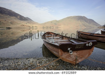 Boats sitting by the lake in a peaceful scene taken at Crummock Water near Buttermere in the English Lake District, Cumbria, England.