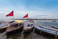 Boats with red flags waiting for devotees on the bank of river Ganges to ferry to Sangam