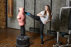 Bob mannequin punching bag in gym helps young smiling woman kickboxer to train kicks.