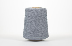 Bobbin of yarn on a white background. Side view. Textile spool on an isolated white background. Close-up.