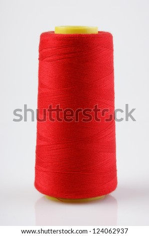 bobbin with red thread on a white background