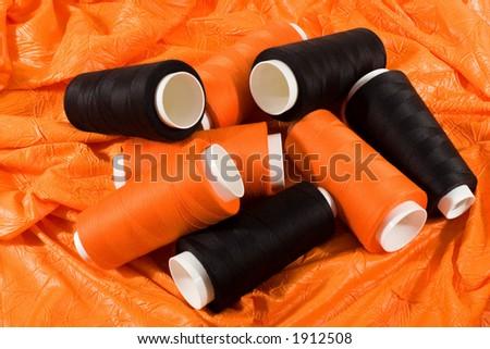 Bobbins of black and orange threads on the orange cloth