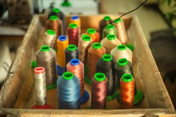 bobbins of thread in a sewing factory, multicolored skeins of thread for industrial sewing, threads for manufacturing, the production process of leather bags and shoes