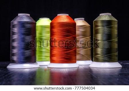 Bobbins of thread on black Background - Shutterstock ID 777504034