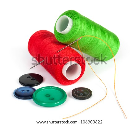 bobbins of thread with needle and buttons isolated on white