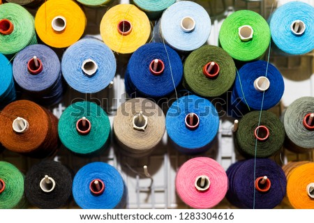 Bobbins with colorful threads on old wooden table background, Sewing background.Interior of sewing workshop.technology, material, equipment, Hobby concept.spools of thread. #1283304616