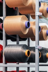 bobbins with threads of different colors on the shelves of a clothing factory or production