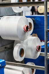 bobbins with white threads on the shelves of a clothing factory or production
