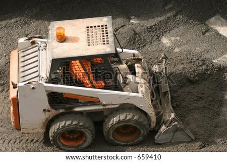 Bobcat scooping up gravel