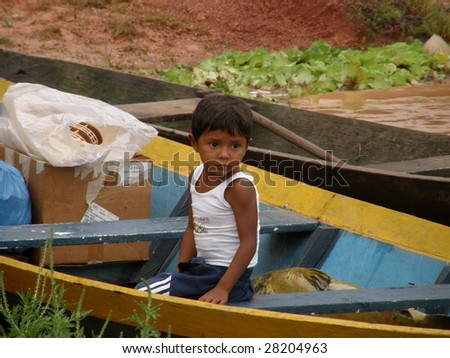 BOCA DE VALERIA: MARCH 11: A young Indian  boy prepares to return home in his canoe after a day of trading on the Amazon River on March  11, 2009, in Brazil - stock photo