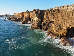 Boca do Inferno, high cliffs feature a natural archway or open cave, created by pounding waves. Steep rocks illuminated by the setting sun. Famous tourist spot, Atlantic ocean shore, Portugal, Cascais