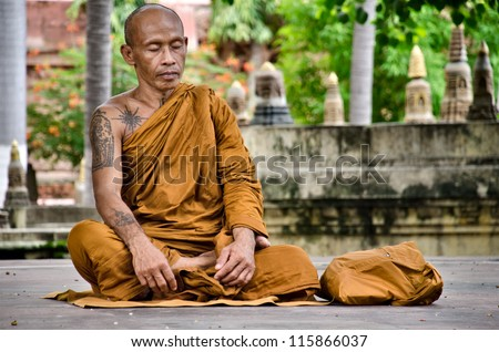 BODGAHYA, INDIA - 9 AUGUST: unidentified monk meditates under a body tree on August 9, 2012. In Bodgahya Lord Buddha was enlightened under a Body tree and now this is a place of worship