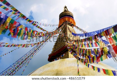 bodhnath stupa in kathmandu with buddha eyes and prayer flags on clear blue sky background