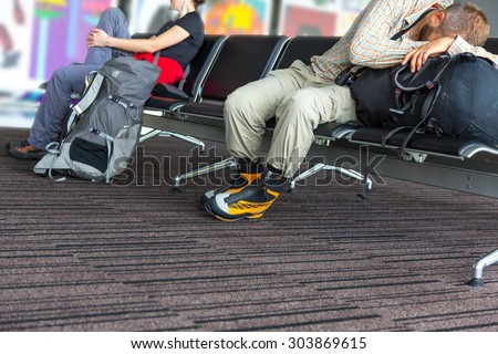 Bodies of people waiting airport terminal. Man and woman sitting at chairs waiting lounge airport building sleep on backpack informal sport dress code pants shirt luggage colorful interior background