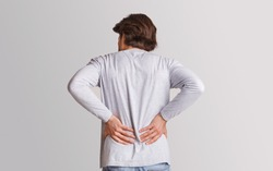 Body ache and kidneys pain. Man presses his hands to back, isolated on gray background, studio shot