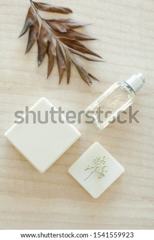 Body and face soap with glass jar of body oil, eucalyptus leaves and containers on natural wooden background #1541559923