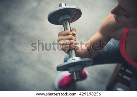 Body and mind workout in loft fitness studio. Closeup on fitness woman workout with dumbbell in urban loft gym #429198256