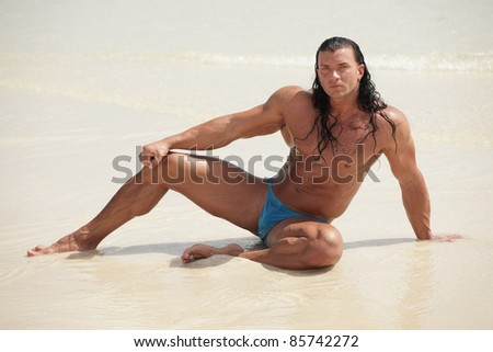 Body builder posing by the ocean shore