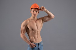 Body builder with fit torso belly chest and arms biceps triceps muscles wear hard hat grey background, bodybuilding.