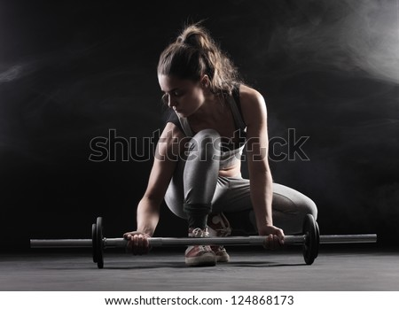 Body building: young woman lifting weights
