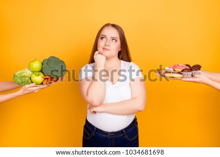 Body care bodycare concept. Confused thoughtful hesitating fatty woman can't make a choice between healthy natural products and sugary tasty biscuits, isolated on bright yellow background #1034681698