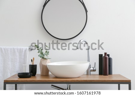 Body care cosmetics with accessories near sink in bathroom
