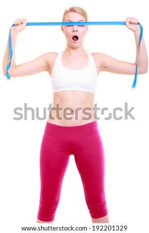 Body care diet and weight loss concept. Fitness surprised girl sporty shocked woman covering her eyes with measuring tape isolated on white