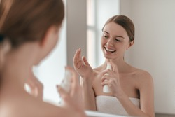 Body care. Over the shoulder view of young beautiful woman applying water spray while standing in front of the mirror
