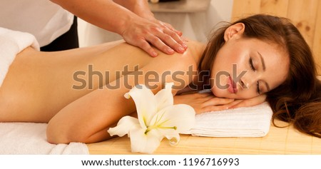 Body care. Spa body massage treatment. Woman having massage in the spa salon. Beb banner dimension image ofmasseur massaging young woman back Foto stock ©