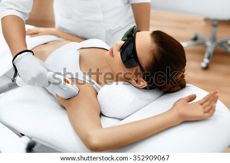 Body Care. Underarm Laser Hair Removal. Beautician Removing Hair Of Young Woman's Armpit. Laser Epilation Treatment In Cosmetic Beauty Clinic. Hairless Smooth And Soft Skin. Health And Beauty Concept.