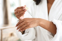 Body Care. Unrecognizable Black Woman Applying Organic Moisturising Serum On Hands Skin, Pampering Herself After Bath, Cropped Image, Closeup