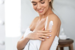 Body Care. Woman Applying Moisturizing Lotion Or Cream On Shoulders Caring For Skin At Home, Standing In Bathroom. Skincare And Pampering, Beauty Routine Concept. Cropped, Selective Focus