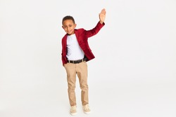 Body language, signs and symbols concept. Full length shot of confident handsome African schoolboy in stylish clothes raising hand, waiving, making greeting gesture, saying Hello, drawing attention
