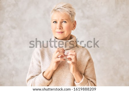 Body language. Studio image of attractive sad mature blonde woman making nervous gesture, frowning eyebrows, stressed with negative news, worrying. Trouble, uneasiness, disturbance and anxiety