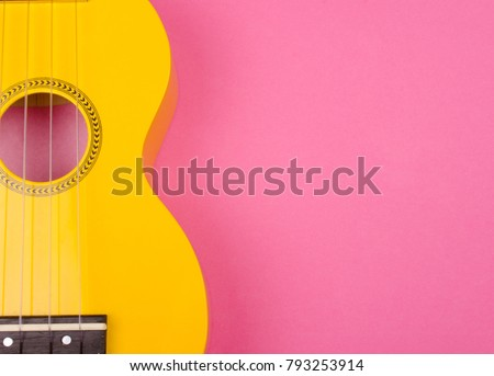 Body of a bright yellow ukulele guitar against a bright pink background (minimalism style), copy space on the right for your text