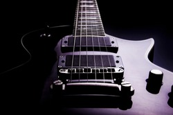 Body of a electric guitar in perspective with black background and purple hue