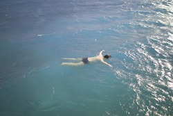 Body of a man floating in the ocean. The lifeless body of a man in the water. Drowned at sea in stormy weather.