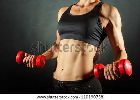 Body of a young fit woman lifting dumbbells on dark background