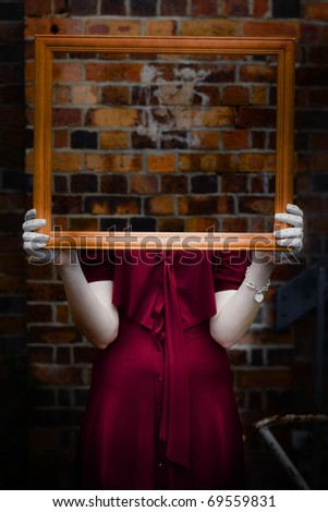 Body Of Ghostly Young Woman Holding Empty Picture Frame With Brick Wall Background
