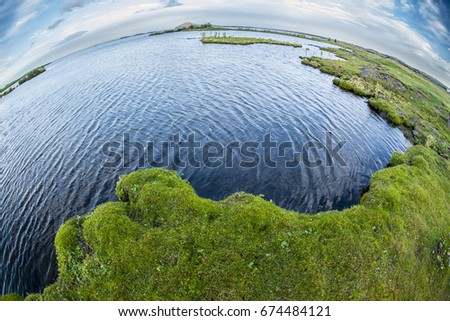 Body of lake water next to a body of grass land