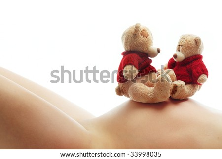 Body of pregnant woman and two teddy bears as a symbol of motherhood