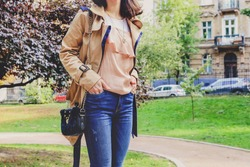 Body of slender woman in a beige coat and blue jeans with a small black handbag. Young girl walking in autumn park. street fashion look, fall outfit concept