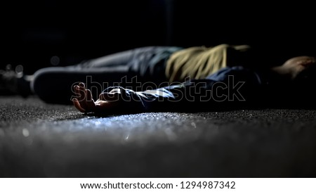 Photo of  Body of woman lying on ground, contract killing, revenge or robbery, horror
